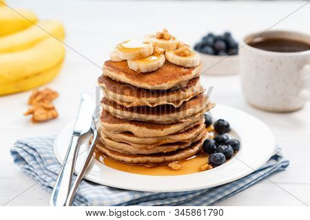 Tasty Pancakes With Banana And Syrup Served With Fresh Blueberries And Cup Of Black Coffee On A Whit