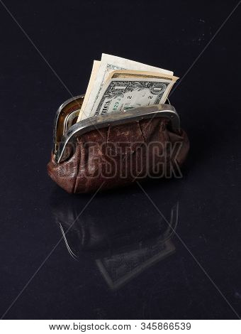 One Open Brown Purse With Dollar Bills Inside On Dark Reflected Background Surface.