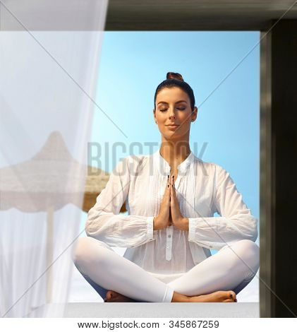 Young woman practicing yoga outdoors, sitting eyes closed in prayer position.