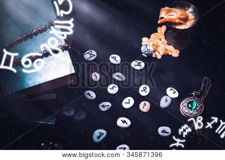 Astrology And Esotericism. On A Black Background Lie Fortune-telling Runes, A Book, An Amulet, And A
