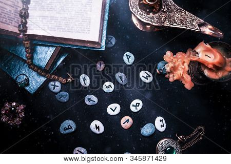 Astrology and esotericism. On a black background lie fortune-telling runes, a book, precious amulets, a copper lamp and a candle. Top view. Dust and light. Close up poster