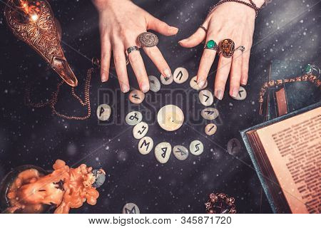 Astrology And Esotericism. Female Witch Hands Conjure Over The Rune Circle. On A Black Background Li