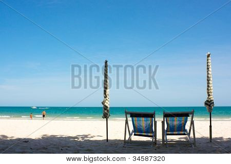 Beach chairs and beach umbrella with clear sky in the summer time