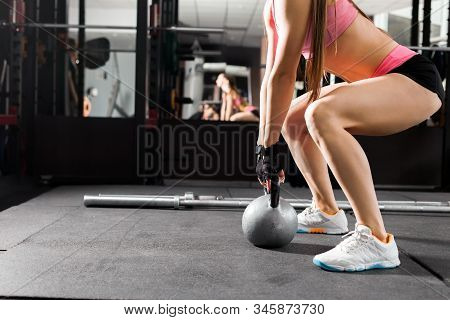 Slim Woman Wearing Pink And Black Professional Sportswear Exercising With A Kettlebell At The Gym. F