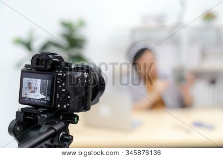 Young asian male IT vlogger and blogger live about Technology upgrand on laptop harddisk using digital camera to recording live vlog video. Online influcencer on social media concept. Focus on camera.