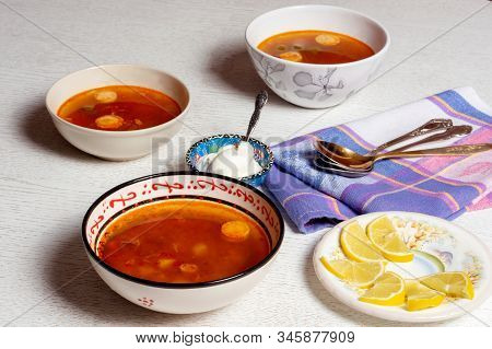 Hodgepodge Soup With Beef Meat, Sausages, Olives, Potatoes Serving With Sour Cream And Pieces Of Lem
