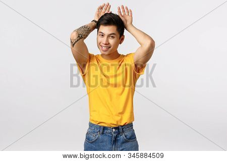 Silly And Cute Young Asian Tattooed Man In Yellow T-shirt, Mimicking Bunny, Showing Rabbit Ears With