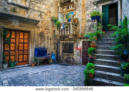 Beautiful Narrow Street With Stone Houses. Old Stone Houses And Entrances Decorated With Flowers. Co