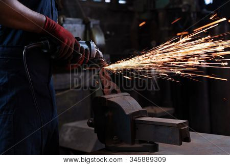 Metal Worker Using Power Tools In Manufacturing Facility, Cutting And Shaping Metal During Work Shif