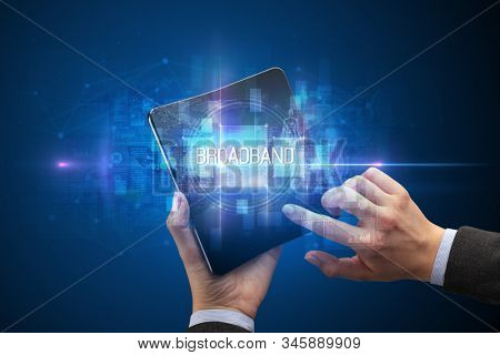 Businessman holding a foldable smartphone with BROADBAND inscription, new technology concept