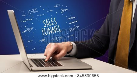 Businessman working on laptop with SALES FUNNEL inscription, online shopping concept