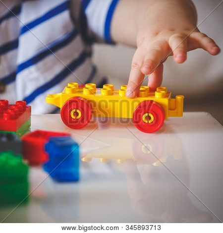 The Kid Plays With Colorful Cubes. The Child Holds In His Hand A Colored Toy With Wheels. Early Deve