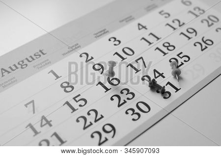 Black And White Monthly Calendar On Table With Office Supplies