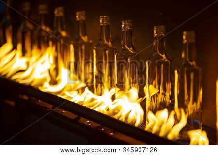 Glassworks. Glass Industry. Making Glass Bottles. Hot Bottle Blanks In Flame