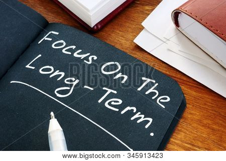 Focus On The Long Term Written On The Black Page.