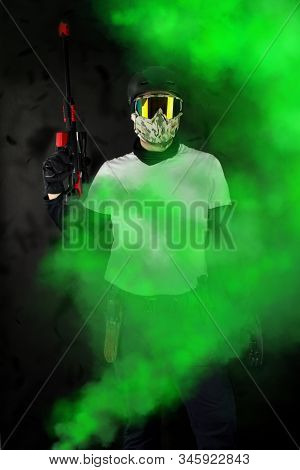 Man With Paintball Helmet And Mask Takes Aim A Gun In Front Of Old Dirty Background.man In Tactical