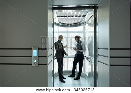 Two young well-dressed male entrepreneurs using mobile gadgets in elevator of modern business center