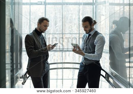 Two young well-dressed businessmen using mobile gadgets at break while standing by window of modern business center