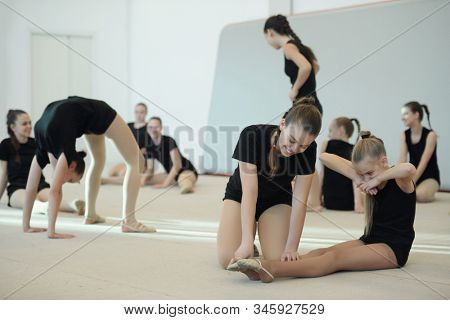 Positive girl with ponytail pushing toes of friend while assisting her to increase toe point at ballet class