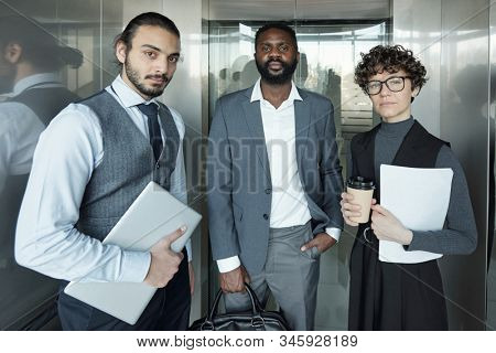 Young serious businesswoman with glass of coffee and paper and two intercultural well-dressed businessmen moving in elevator