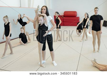 Young female coach assisting flexible girl to do split standing on one leg while other girls performing warm-up exercises