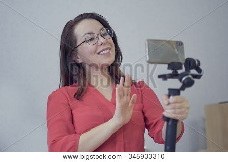 Attractive Asian Woman Blogger Or Vlogger Looking At Camera And Talking On Video Shooting With Techn