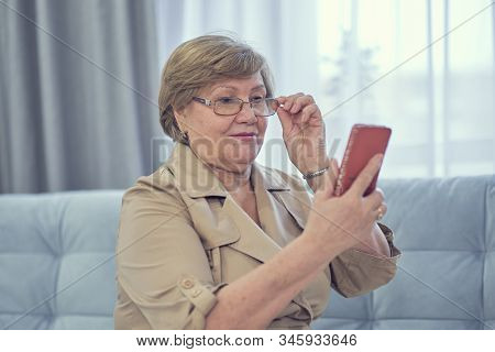 Senior Woman Wearing The Spectacles, Holding A Smartphone In Hand At Garden Background. Online Shopp