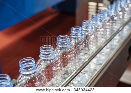 The Pet Bottles On The Conveyor Belt For Filling Process In The Drinking Water Factory. The Drinking