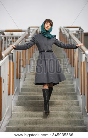 Young fashion woman leaning on railing on steps Stylish female model in gray classic coat and head scarf