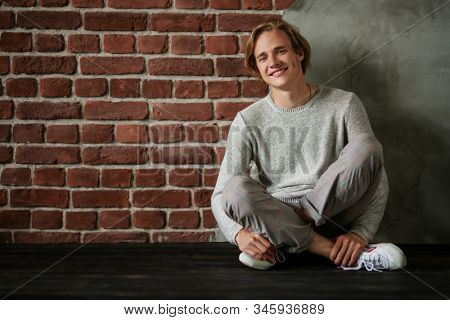 A portrait of a young goodlooking man sitting on the floor. Casual men fashion.