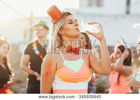 Brazilian Carnival. Woman In Costume Drinking Water