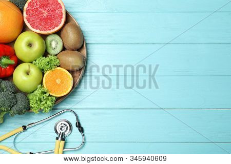 Fruits, Vegetables And Stethoscope On Light Blue Wooden Background, Flat Lay With Space For Text. Vi