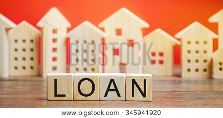 Miniature Houses With The Word Loan. The Concept Of Mortgage Housing And Real Estate Loans. Buy An A
