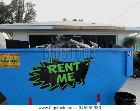 A Rental Roll-off Dumpster Is Filled With Old Shingles And Other Debris From A Roof Replacement On A