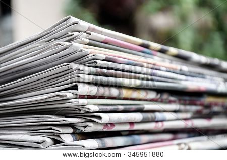 Newspapers Folded And Stacked On The Table With Gardenor Green Background. Closeup Newspaper And Sel