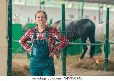 Portrait Of Female Rancher At Horse Stable Looking At Camera. Adult Woman Wearing Plaid Shirt And Je