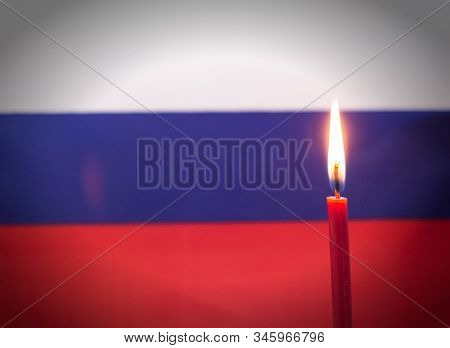 Burning Candle On The Background Of The Flag Of Russia. The Concept Of Mourning And Sorrow In The Co