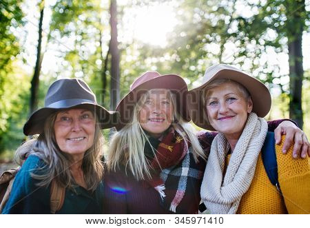 Senior Women Friends Walking Outdoors In Forest, Looking At Camera.