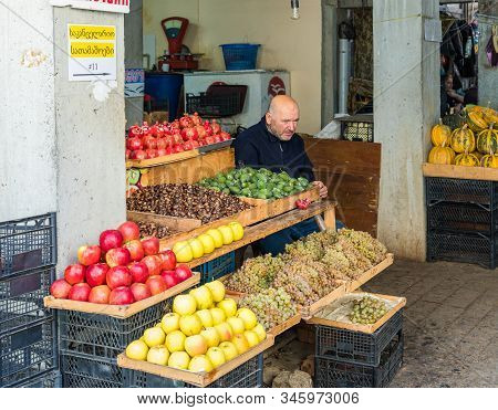 Kutaisi, Georgia, October 13, 2019 : A Seller Sits Near His Fruit Tray In A Market In The Old Part O