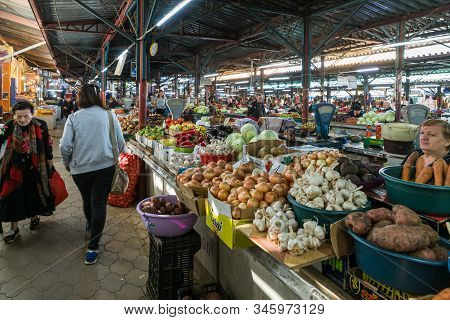 Kutaisi, Georgia, October 13, 2019 : The Seller Sits Near His Counter With Vegetables And Fruits In