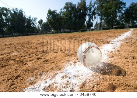 A baseball lies in the chalk line of a baseball field. poster