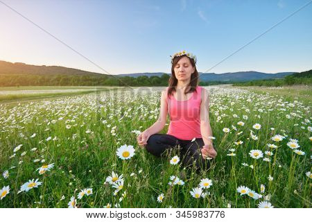 Girl meditates in lotus pose on green camomile meadow. Practicing of yoga at summer. Portrait of young peaceful woman. Training and meditation outdoor. Healthy lifestyle.