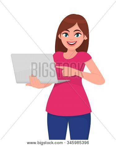 Young Woman Holding A New Laptop Computer And Pointing Finger. Trendy Girl Using Latest Digital Devi