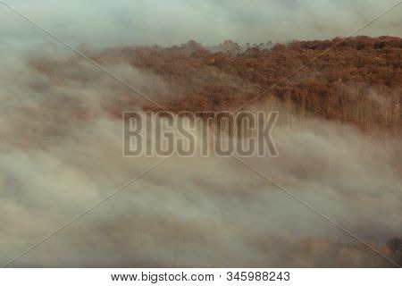 Autumn Inverse Clouds Cover The Landscape. From The Fog They Pull Out The Tree Crowns