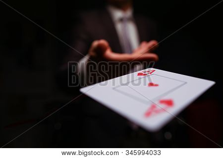 Close-up Of Man In Presentable Suit Throwing Playing Card Ace Of Hearts To Opponent On Dark Backgrou