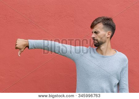 Young Bearded Man Showing Thumb Down On Red Wall Background. Male With Negative Expression And Disap
