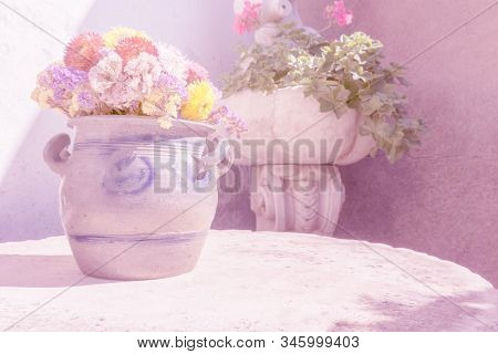 Flowers In Ceramic Vase On Stone Table And Other Flowers In Stoneware Vase On Wall Background. Pink
