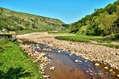 Rocky riverbed and clear water of the River Swale as it flows along the valley floor between the rolling hills of the Yorkshire Dales England poster