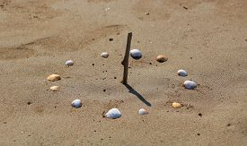 Sundial Made With Seashells On Beach, Close Up