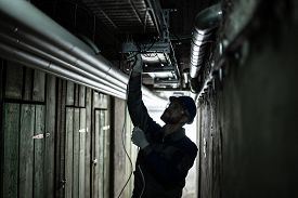 Silhouette Of A Male Electrician Installing Light At Basement